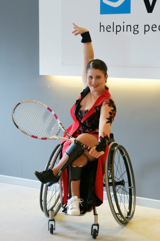 Sofie Cox - Posing in the wheelchair wearing a dance dress and holding a tennisracket